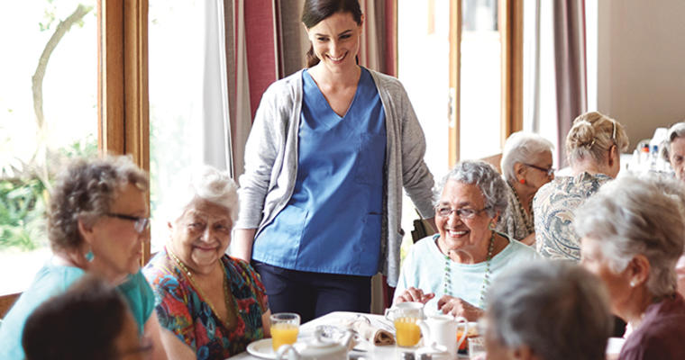 server talks to seniors at a nursing home dining table